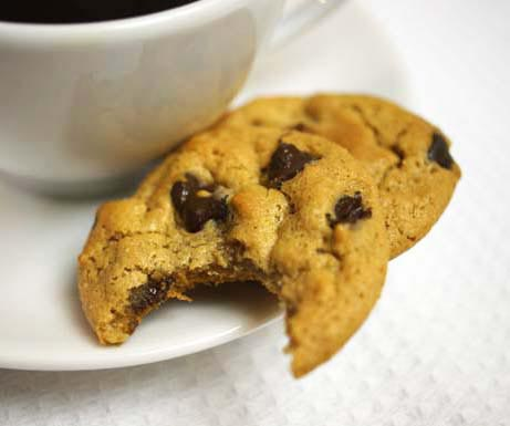 peanut butter chocolate chip cookie with coffee and bite taken