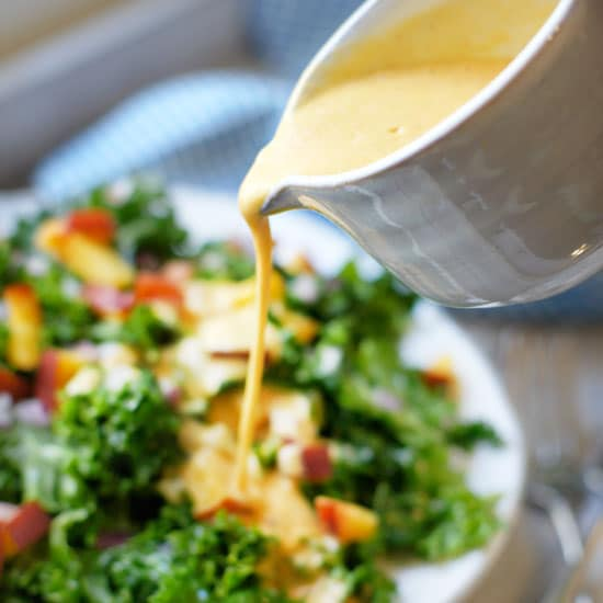 pouring dressing over kale peach salad