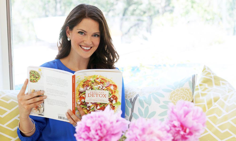 Megan holding everyday detox cookbook