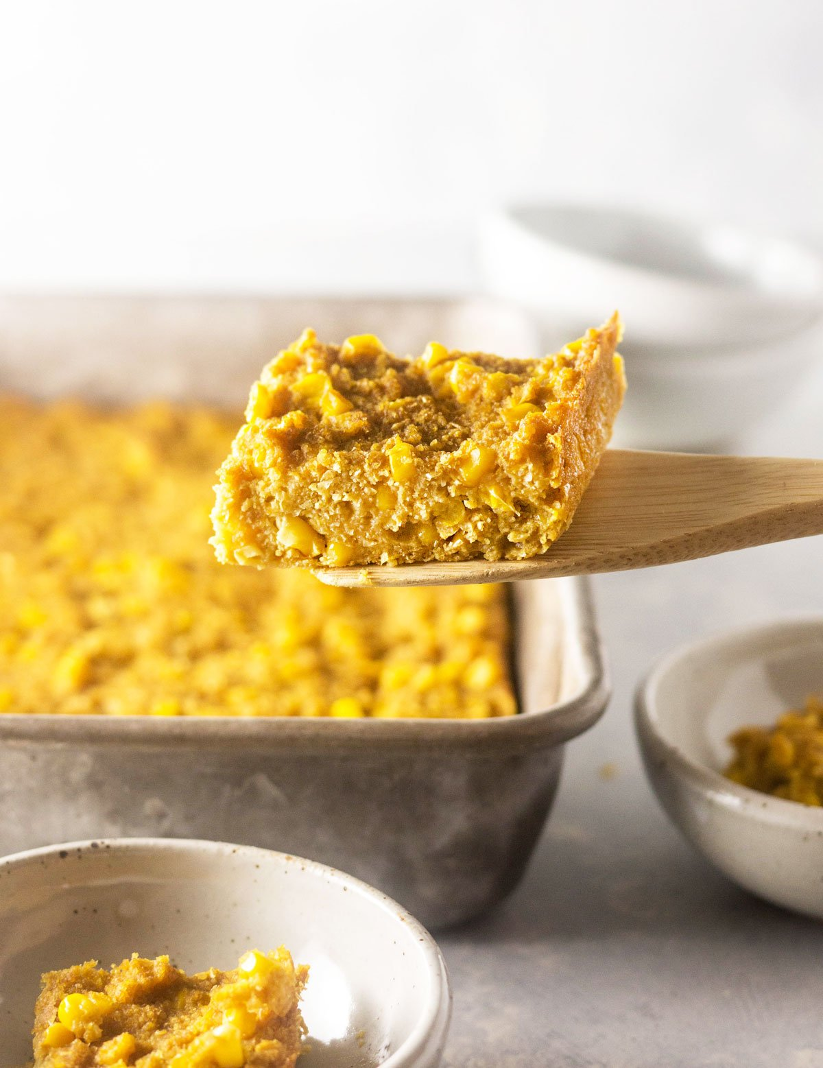vegan corn casserole being scooped out of a pan