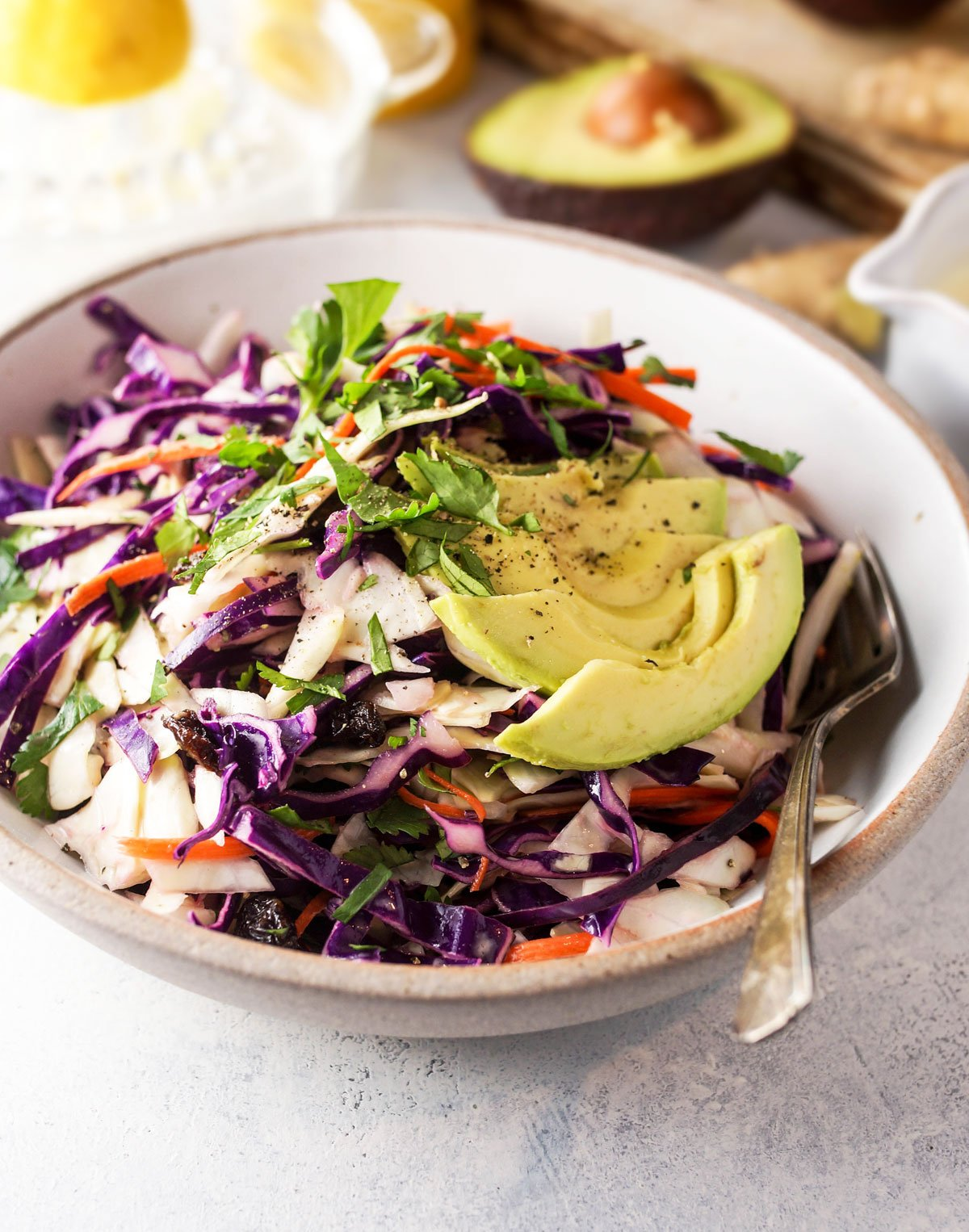 bowl of detox salad with lemon ginger dressing and slices of avocado on top