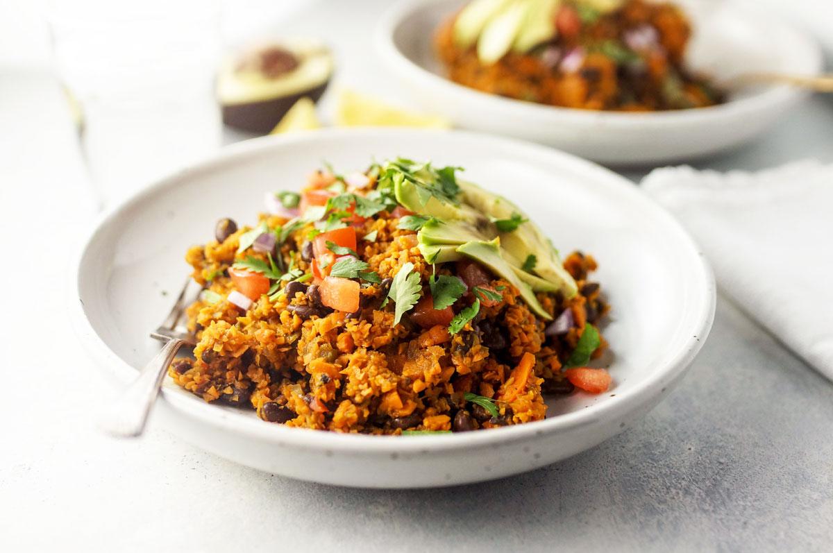 vegan sweet potato rice burrito bowl in white bowl with avocado in background