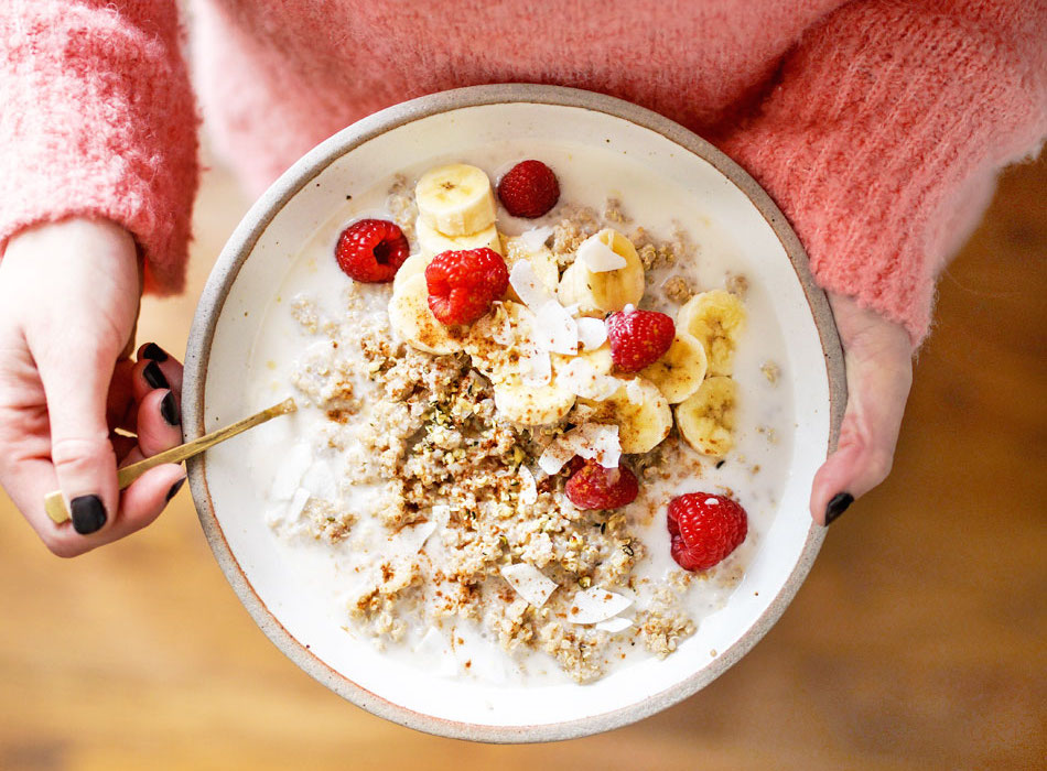 holding a bowl of quinoa breakfast with raspberries and bananas on top