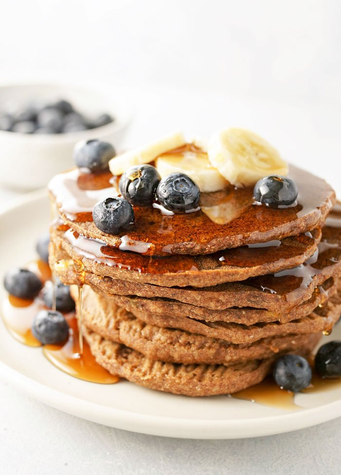 stack of baked buckwheat banana pancakes with blueberries, bananas, and syrup on top