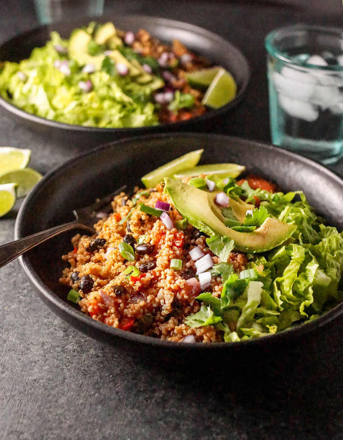 Instant Pot Vegan Quinoa Burrito Bowls on a plate with avocado slices on top