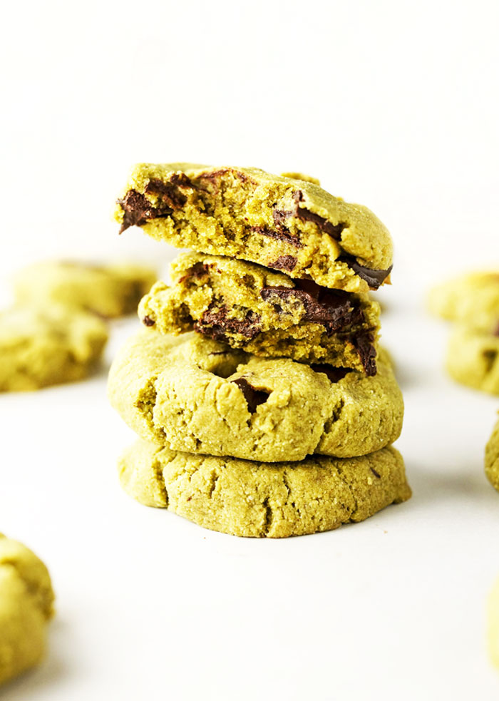 stack of matcha mint chocolate chip cookies with the top cookie split in half