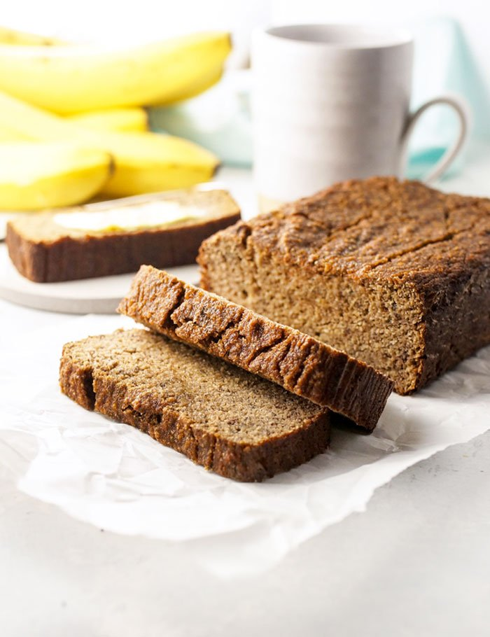 coconut flour banana bread loaf sliced with bananas and a coffee mug behind it