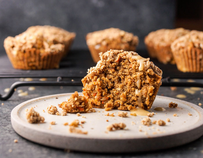 half of a gluten-free carrot cake muffin on a plate