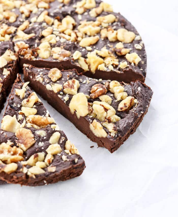 a slice of vegan chocolate fudge cake topped with walnuts