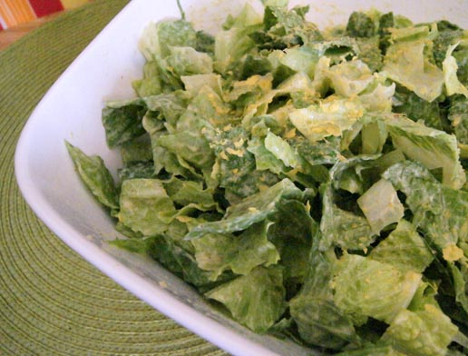 tossed salad with dressing topped with nutritional yeast
