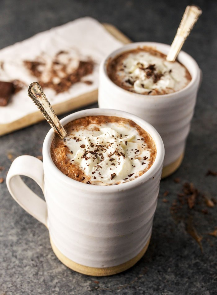 two mugs of dairy free hot chocolate with a spoon and whipped cream in each mug
