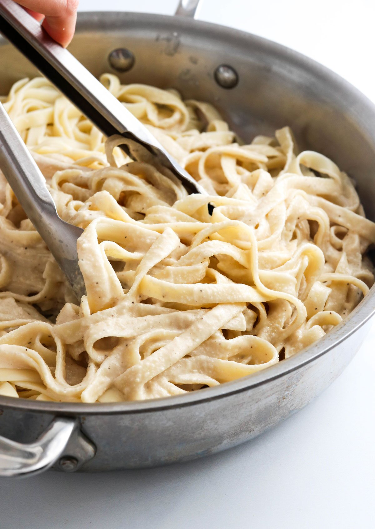 alfredo sauce tossed with pasta in pan