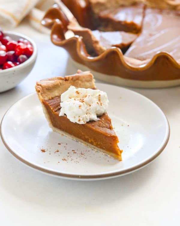 vegan pumpkin pie slice topped with coconut whipped cream