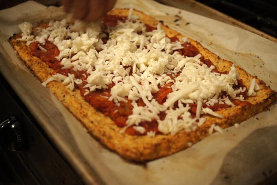 putting sauce and cheese on top of cauliflower pizza crust