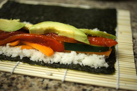 sliced veggies layered on top of rice and sushi paper
