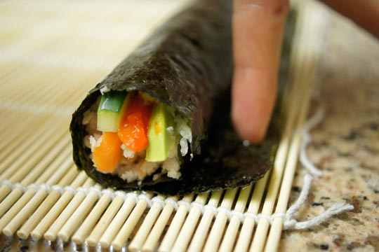 finger spreading water on edge of rolled sushi paper