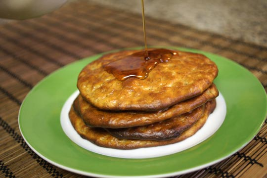 paleo pancakes stacked on a plate with syrup poured on top