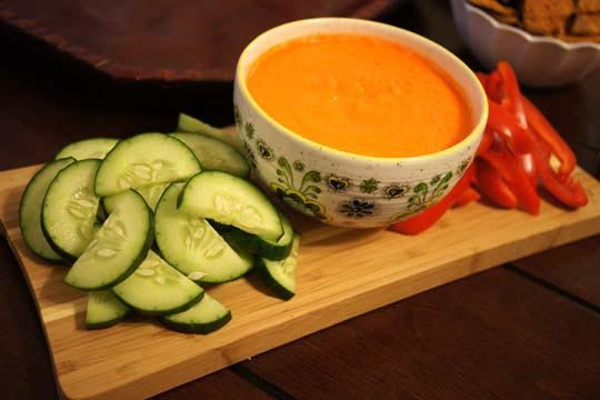 bowl of carrot ginger dip and cutting board with cucumber slices and red pepper slices