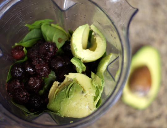 cherry chocolate avocado smoothie ingredients in a blender