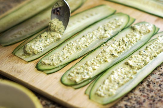 spreading hummus on cucumber slices