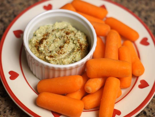 bowl of hummus and baby carrots on a plate