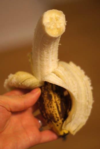 hand holding a peeled banana