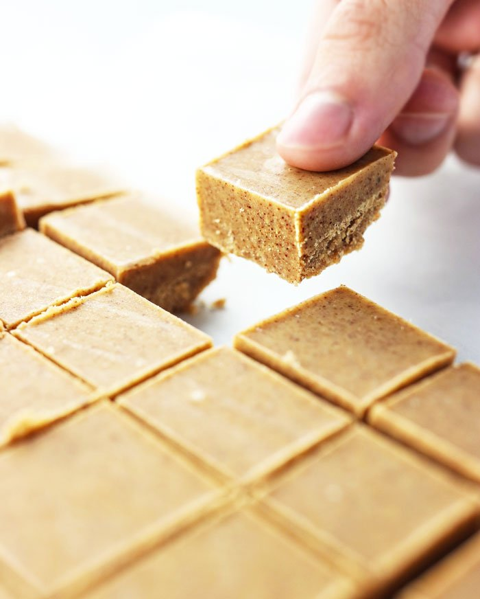 hand picking up an almond butter fudge slice