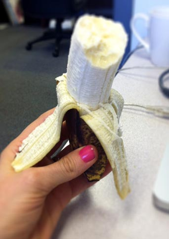 hand holding a peeled banana with a bite taken out of it