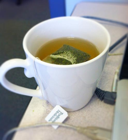 white mug with a tea bag and hot water
