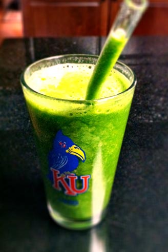green smoothie in a KU glass with a straw in it