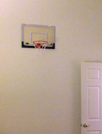 small basketball hoop hanging on the wall