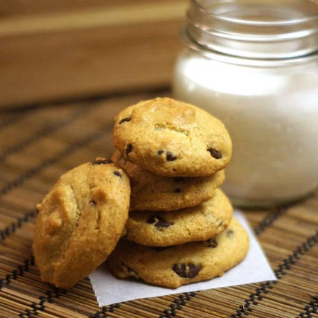 stack of chocolate chip cookies with a glass of milk behind them