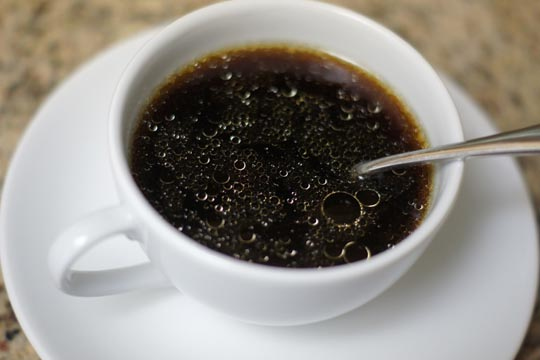 cup of black coffee with a spoon in it
