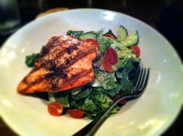 salad on a plate with a piece of grilled salmon on top