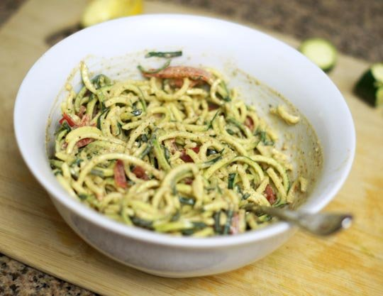 zucchini noodles in a bowl with dressing mixed in