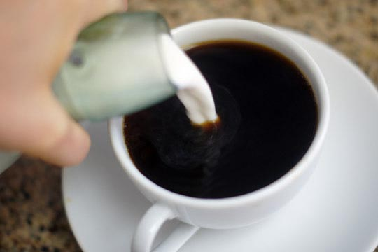 pouring creamer into a cup of coffee