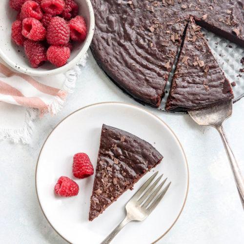 flourless chocolate cake slice on plate with raspberries