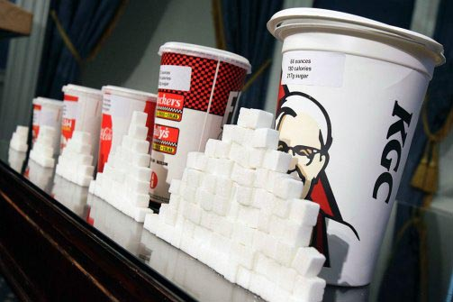 sugar cubes stacked in front of soda cups
