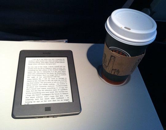 kindle and a cup of coffee on a table