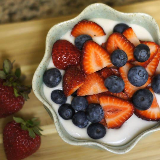 coconut cream pudding in a bowl with sliced strawberries and blueberries on top