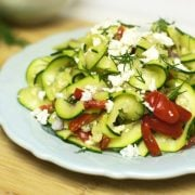Mediterranean zucchini pasta salad topped with dill and cheese