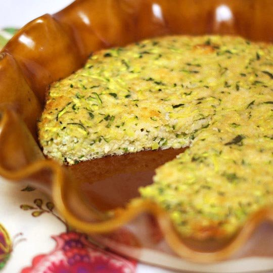 flourless zucchini pie in a pie dish with a slice cut out of it