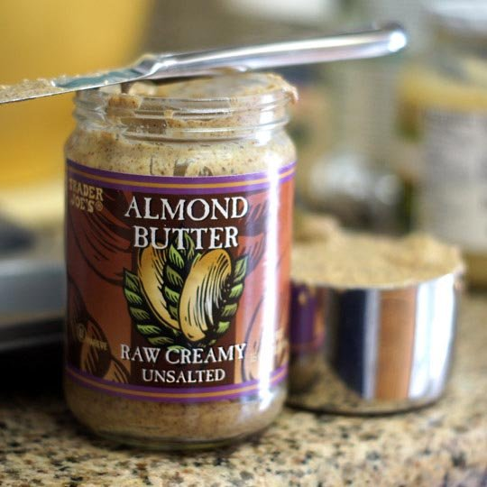 jar of almond butter scooped into a measuring cup