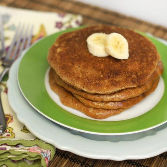 stack of almond butter pancakes on a plate with banana slices on top