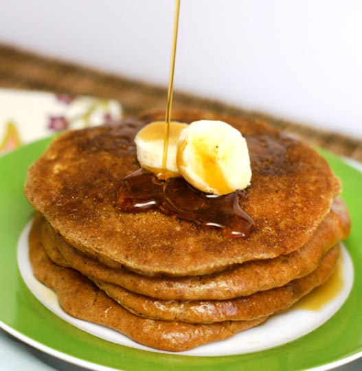 stack of almond butter pancakes on a plate with banana slices and syrup on top