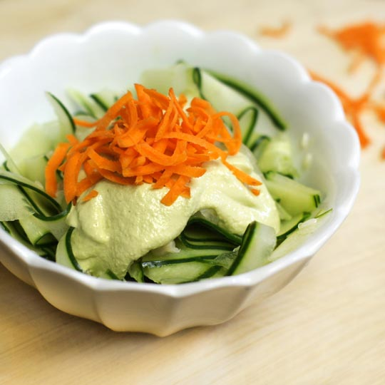 bowl of zucchini noodles with green goddess dressing and carrot slivers on top