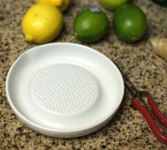 a ceramic grater with lemons and limes next to it