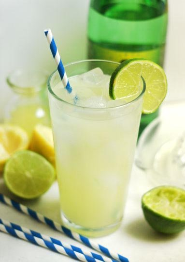 glass of sugar-free gingerade with a straw and a slice of lime