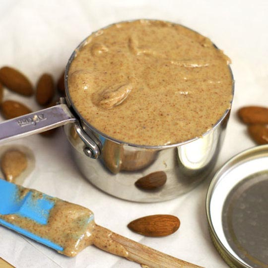 a measuring cup of homemade almond butter with a spatula and almonds