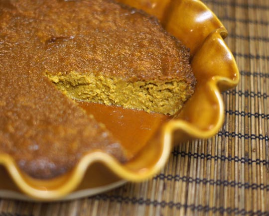 vegan pumpkin pie in a pan with a slice cut out of it